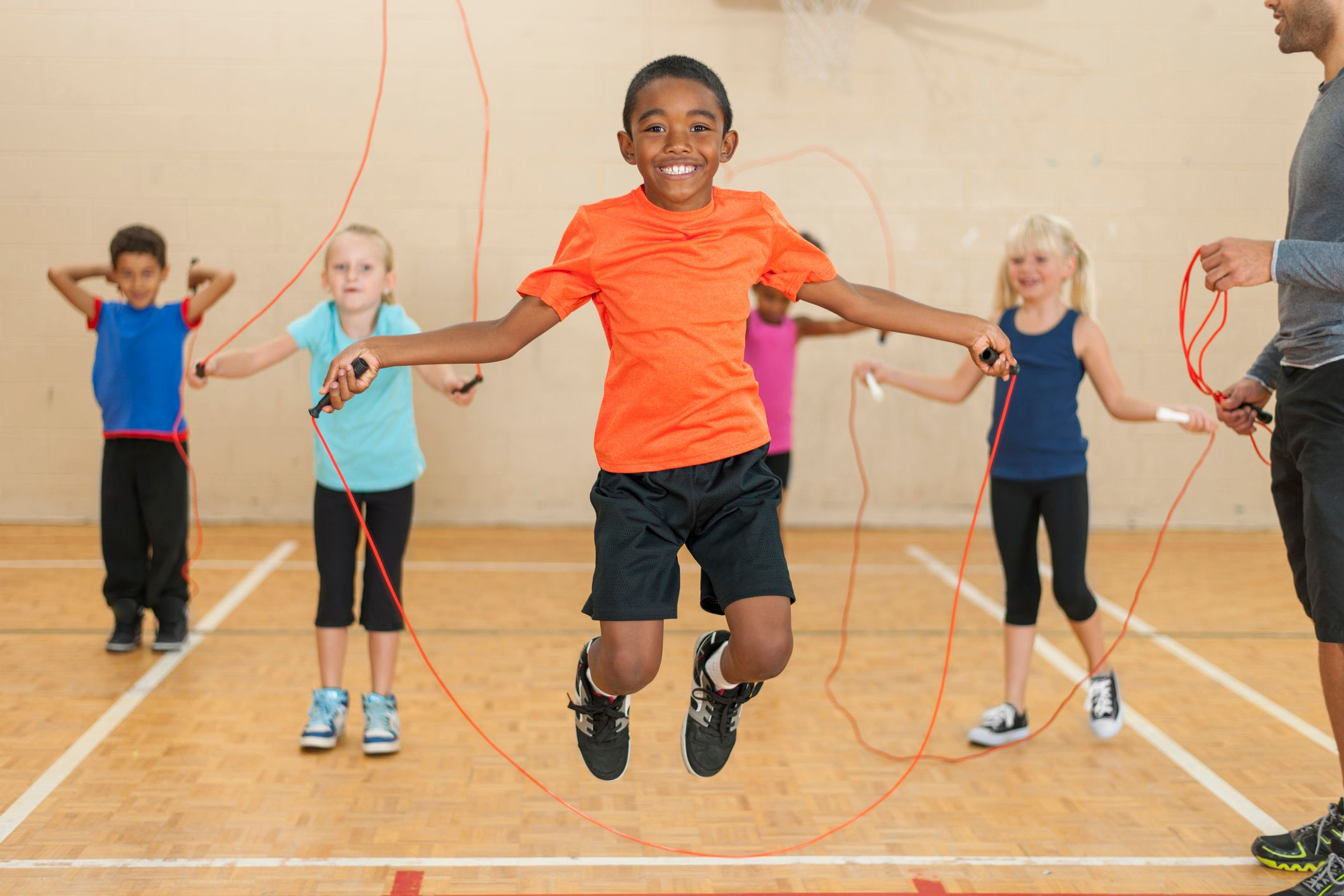 Students in school gym with jump ropes.