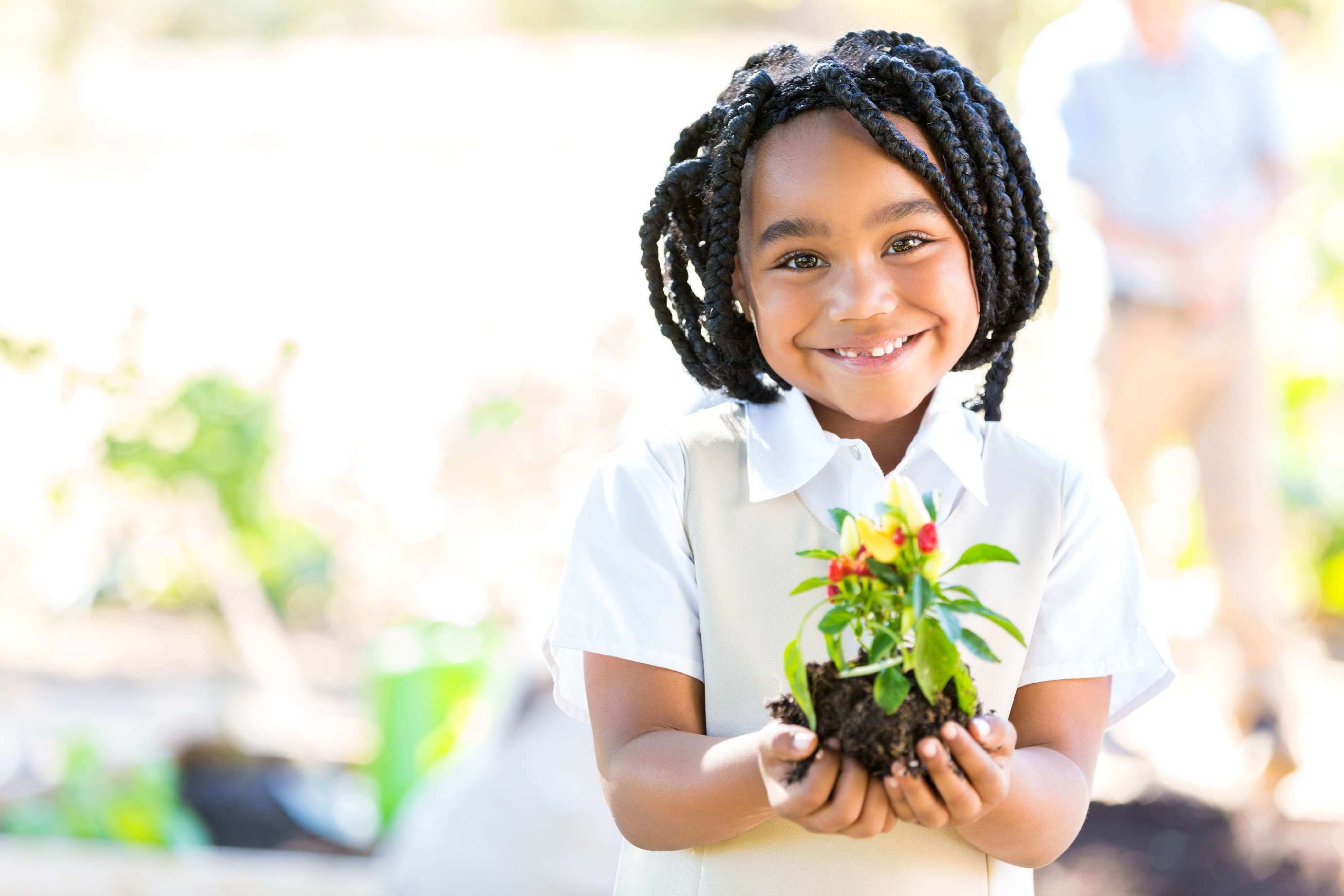 Student holding flower with both hands.